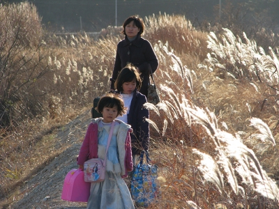 A mother and her two children walk down a path amid stalks of wheat, whitened by the bright sun
