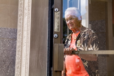 an older white-haired man in an orange shirt and gold eagle pin exits a building