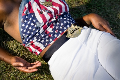 torso of a woman lying in the grass, wearing white pants and an American flag halter top