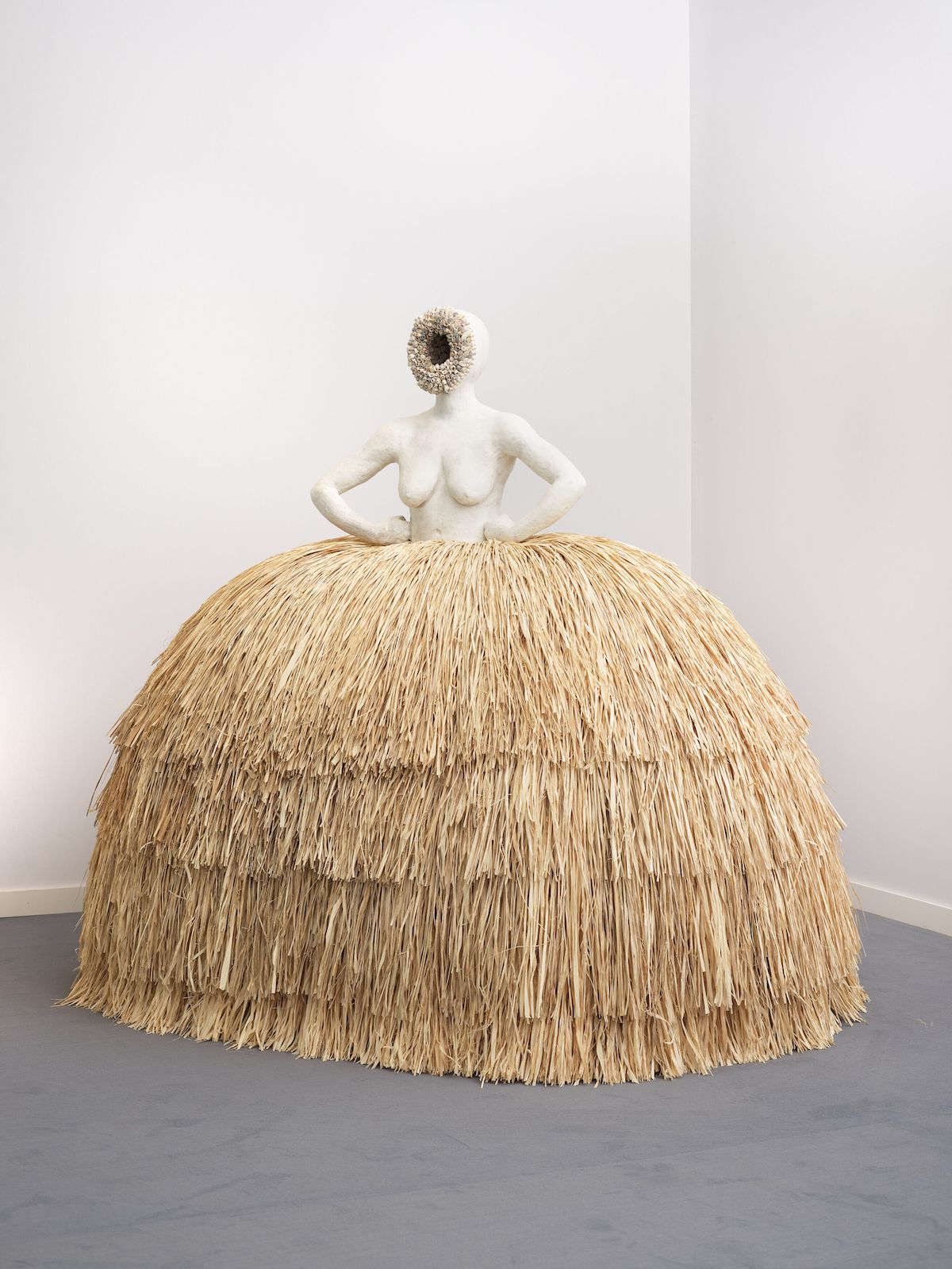 Simone Leigh, 'Las Meninas', 2019. A female form with a missing face holds her hips above a raffia dress.
