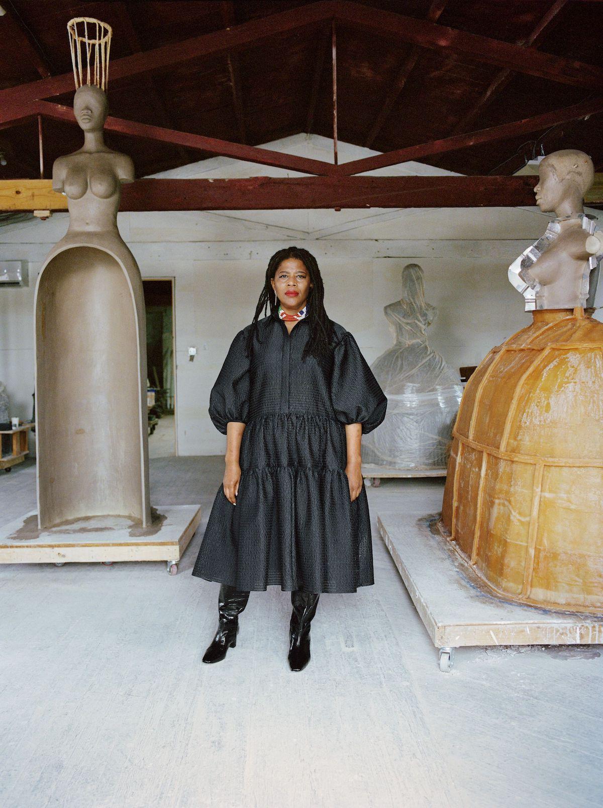 Simone Leigh Portrait standing in her Studio amid sculptures