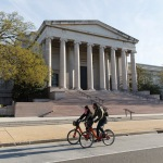 Cyclists ride past the National Museum