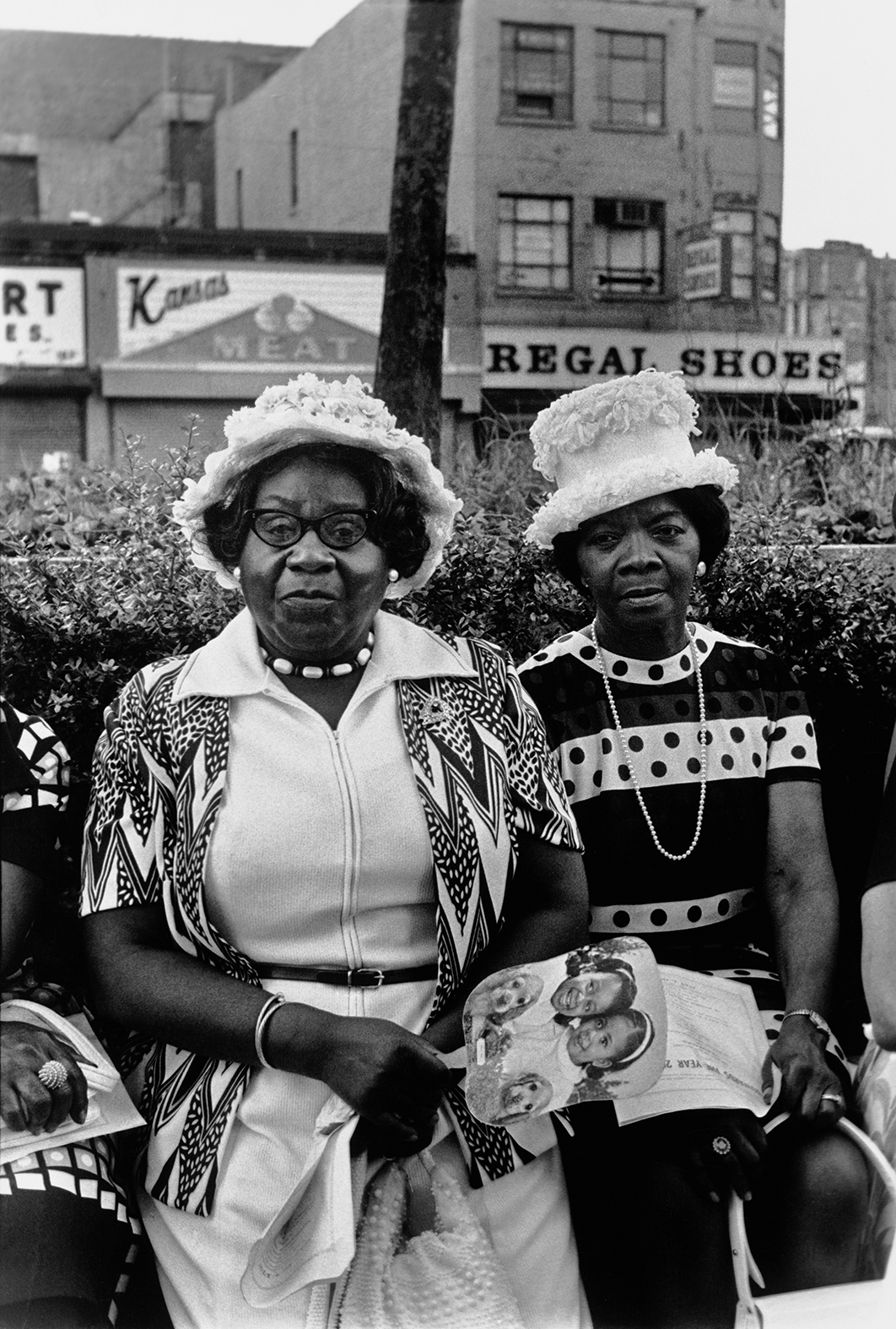 Ming Smith, 'Amen Corner Sisters, Harlem, New York', 1976. Two women sit on a bench before Harlem shops.