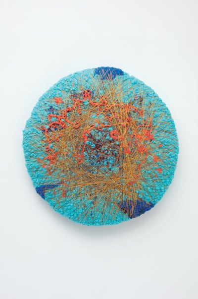 Sheila Hicks, L'encinte, 2018. A circle fabric artwork of mostly turquoise color with pops of orange in center and dark blue on the sides.