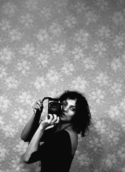 Ming Smith, 'Self-portrait', ca. 1988. A woman clutches a camera next to her face as she shoots her image through a mirror.