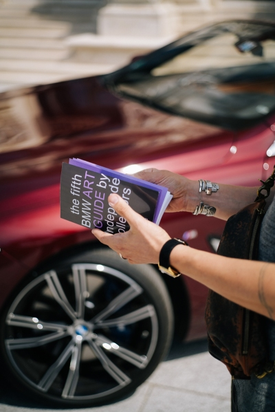 A person holding the fifth edition of the BMW Art Guide by Independent Collectors in front of red BMW.