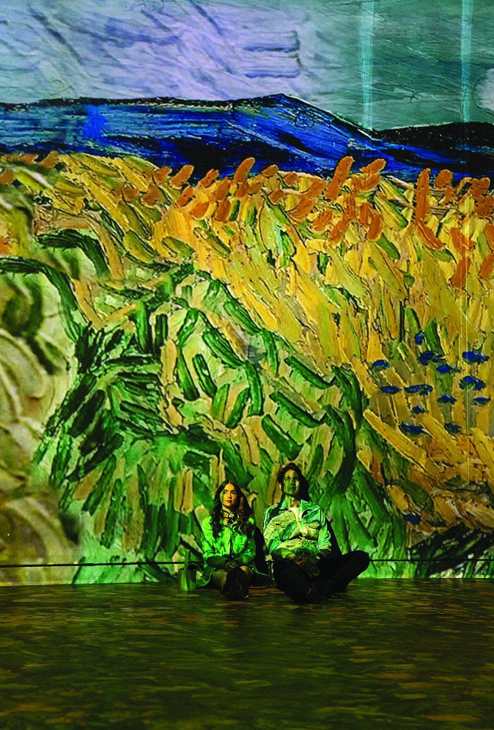 A digital projection of a Van Gogh painting covers a wall and two people leaning against it with thick brushstrokes of green and gold