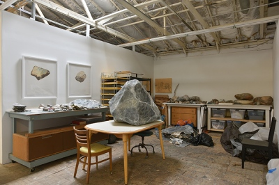 Interior shot of an artist's studio, with rocks of varying sizes on surfaces and framed drawings of rocks on one wall
