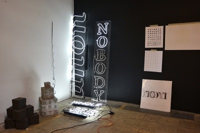 Interior shot of an artist's studio, with white neon text pieces leaning against a black wall