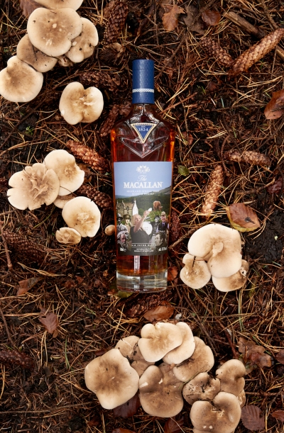 An Estate, A Community, and A Distillery whisky, a collaboration between Sir Peter Blake and The Macallan. The whisky is photographed in a field surrounded by mushrooms .