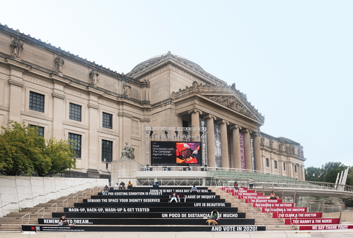 Exterior of the Brooklyn Museum in 2020, with a lettering campaign on its steps, encouraging people to wear masks and vote, among other things.