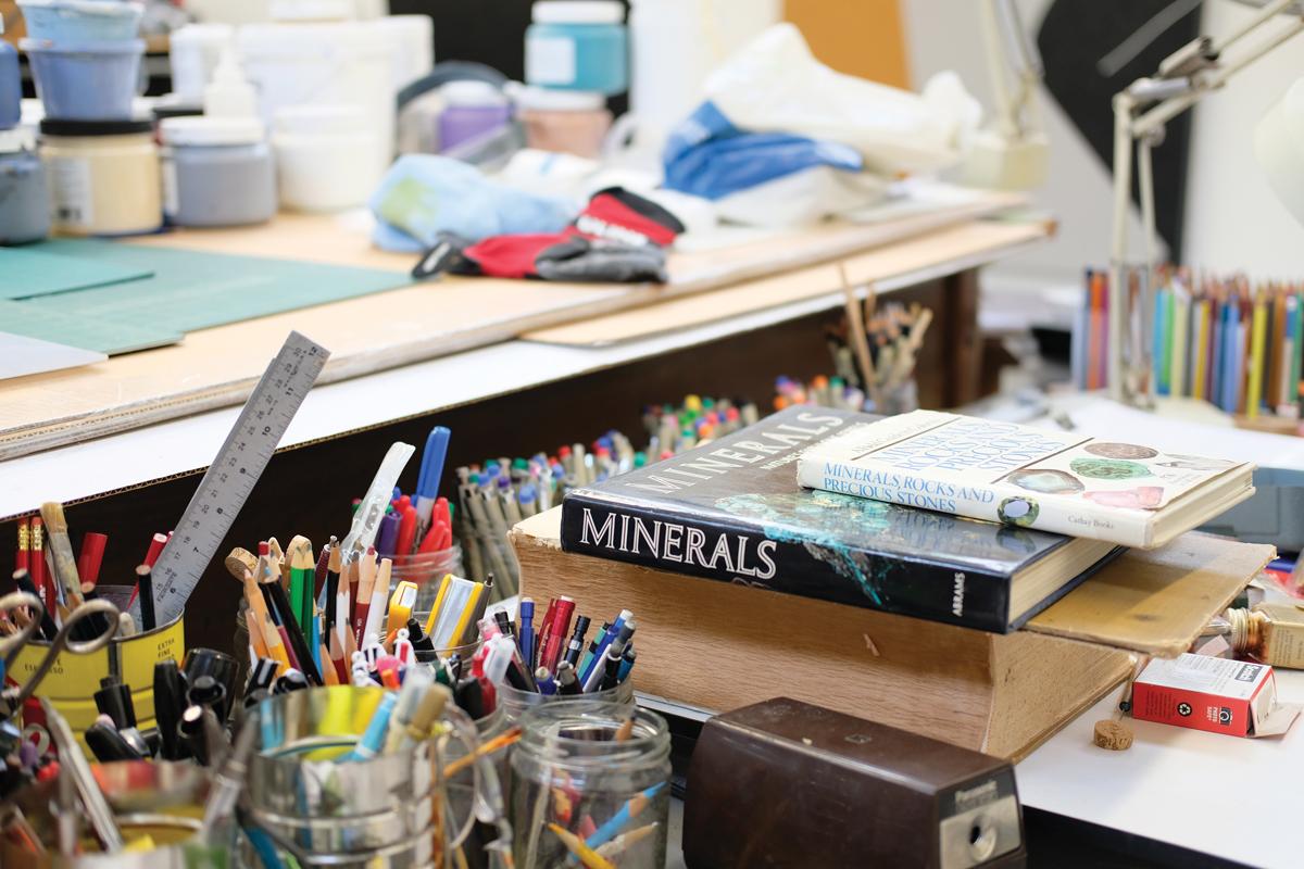 In Jaramillo's studio are dozens art materials and books on minerals.