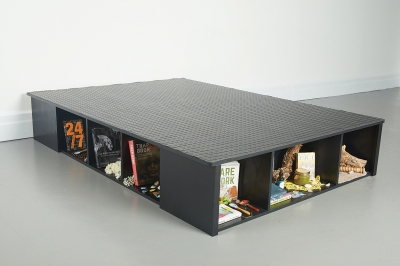 On a grey floor, against a white wall is a black bed frame shot at a three quarter angle. The bed frame has built-in storage cubbies, six are visible. Inside of each cubby are various objects and ephemera, all intentionally placed, sculptures within the sculpture. Some of the objects that are visible include books such as Care Work: Dreaming Disability Justice by Leah Lakshmi Piepzna-Samarasinha and 24/7: Late Capitalism and the Ends of Sleep by Jonathan Crary, rocks, a jar of salve, and the fuzzy surface of a heating pad. In the place of a bed is industrial black diamond plate rubber flooring cut precisely to the dimensions of the bed frame and laid flat across the surface. The diamond plate creates a textured patterned surface.