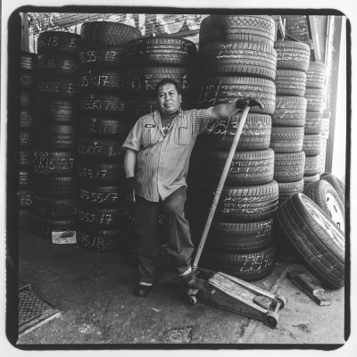 "Bronx Photo League/Bronx Documentary CenterImages from Jerome Ave Workers Project. Josè Cruz, a mechanic at Diffo Auto Glass & Flat Fix, 1510 Jerome Avenue. Josè has been working on Jerome Avenue for 25 years--he fled the civil war in his native El Salvador in 1990. Photo taken June 27th, 2015 by David ""Dee"" Delgado and Michael Kamber/Bronx Photo League"