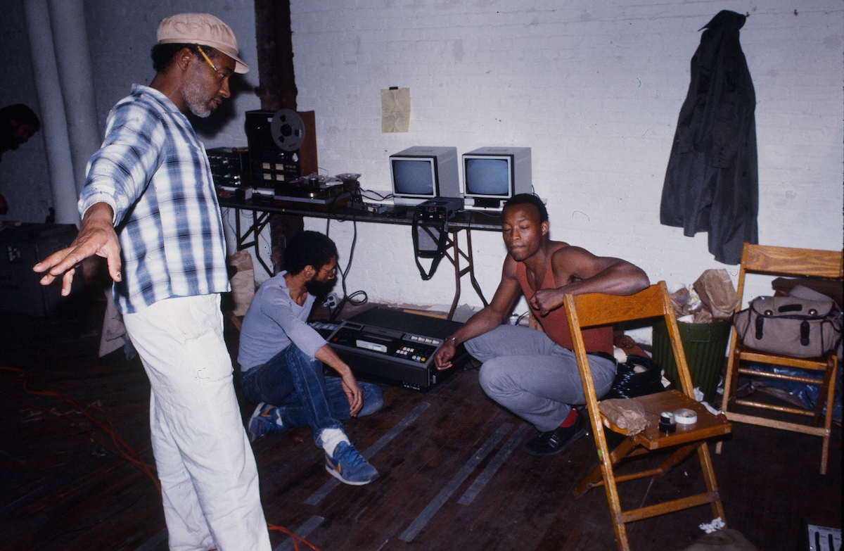David Hammons (at left) at Just Above Midtown in 1983. Several men are shown in a gallery near two monitors. One crouches to the ground, one is seated, and one stands.