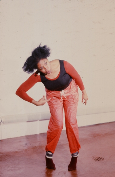 Senga Nengudi performing at Just Above Midtown in 1981. A woman contorts her face as she bends over with her hand on her hip.