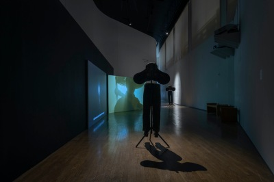 A sculpture consisting of a saddle and a pair of pants stands in the foreground, while a two-channel video depicting a person holding a pick-axe is visible in the background.