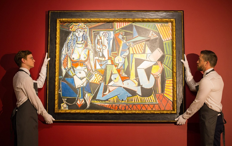 Picasso's Femmes d'Alger painting hung on a red wall with two men in white dress shirts and black aprons holding it up