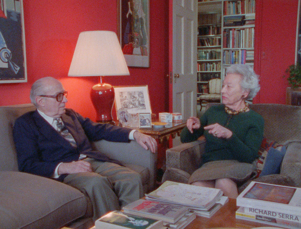 Victor and Sally Ganz on couches in their living room full of art and books