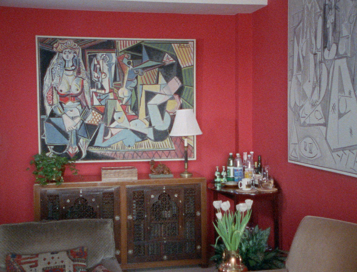 apartment interior with red walls and Picasso's painting Les Femmes d'Alger (version O) on the wall