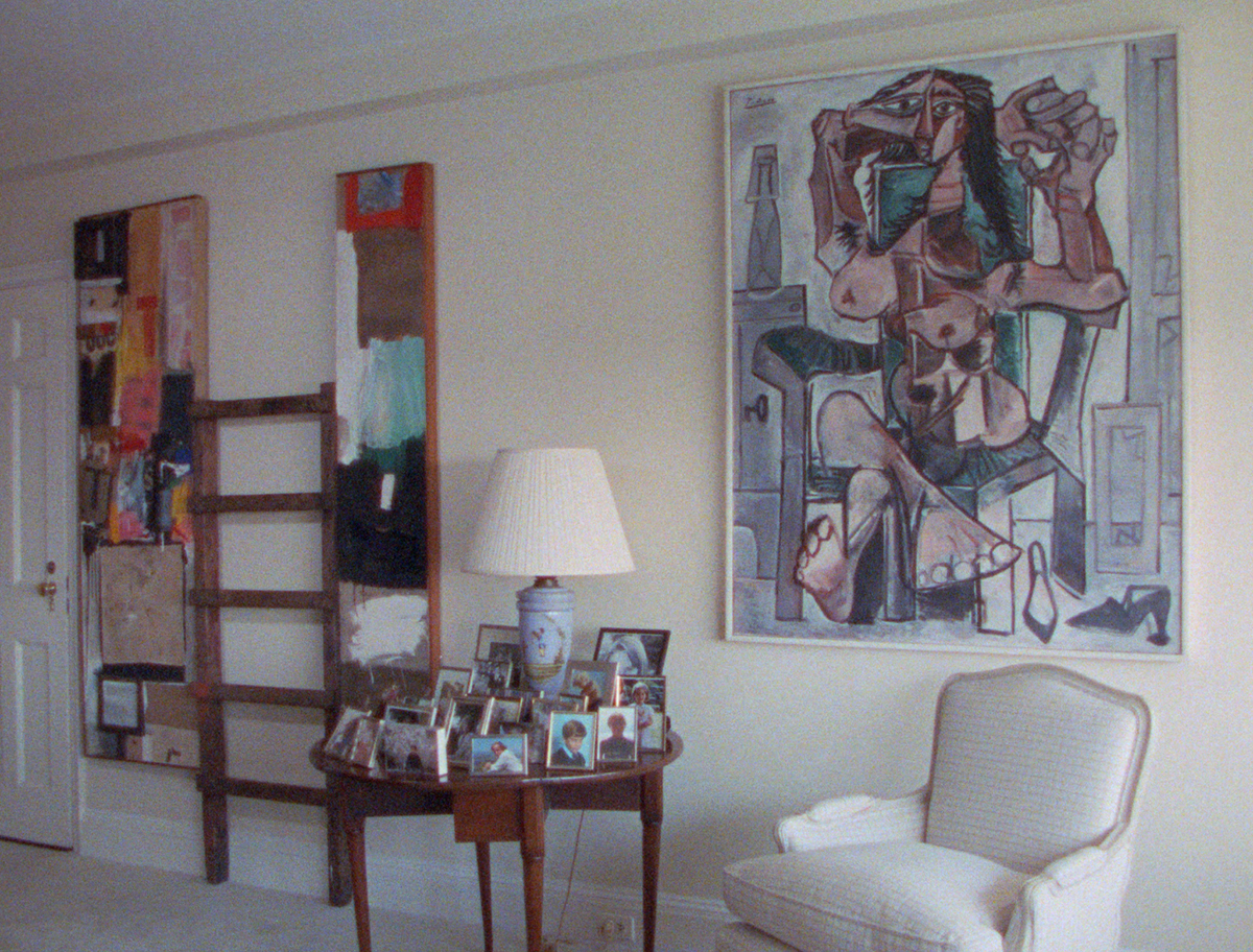 living room with two artworks and a table covered with framed photos
