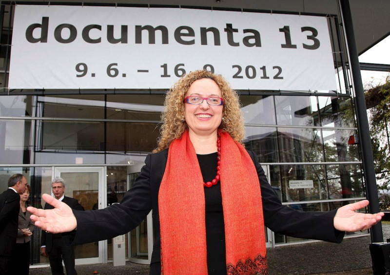A woman wearing a pink scarf stands with her hands outstretched. Behind her is a banner reading 'documenta 13.'