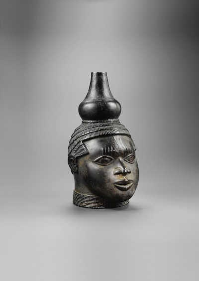 A bronze sculpture of a head with a decorative ornament at the top.