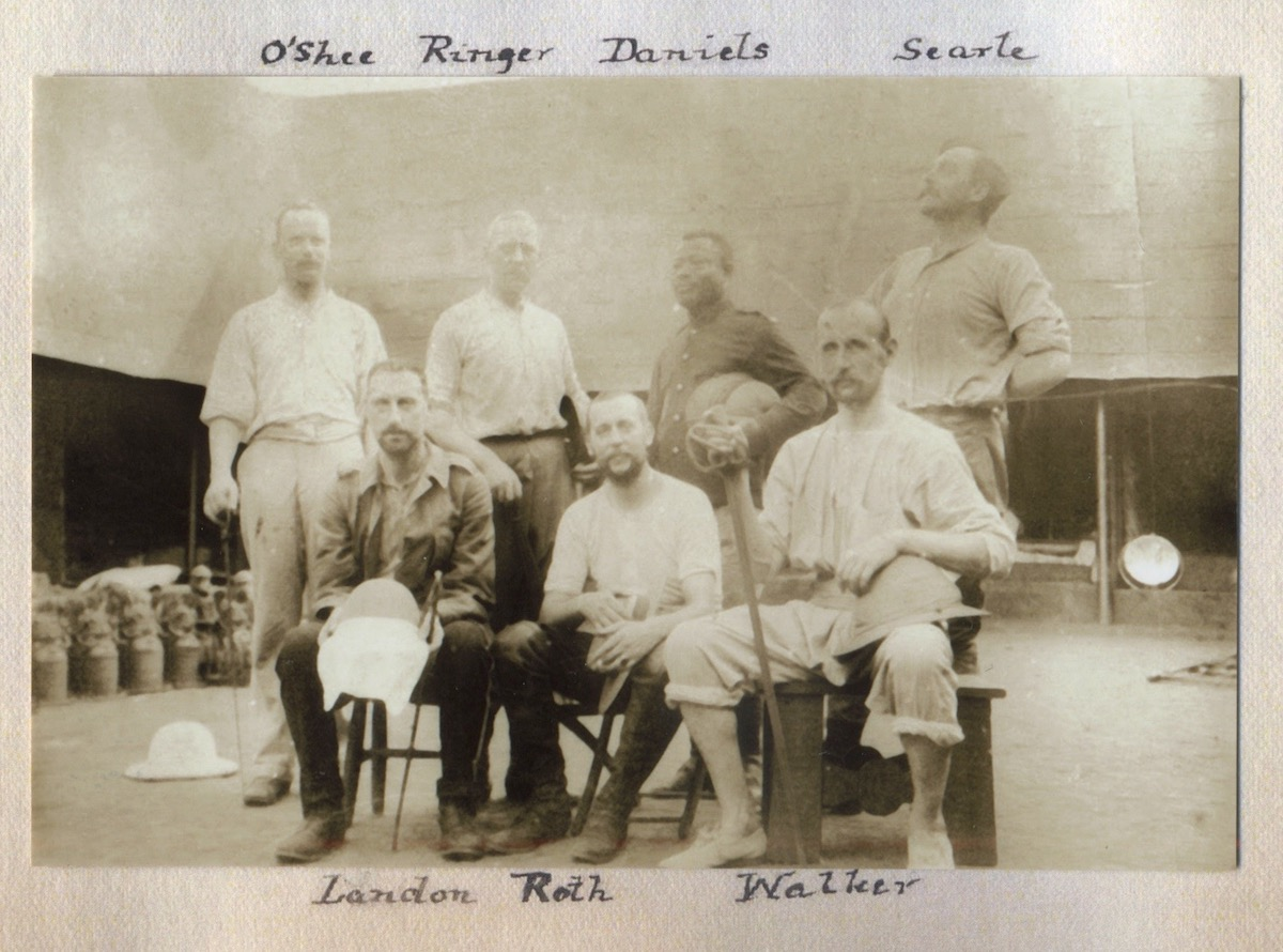 A group of men pose for a picture. Some are seated while others stand. Behind them is the Oba's palace.