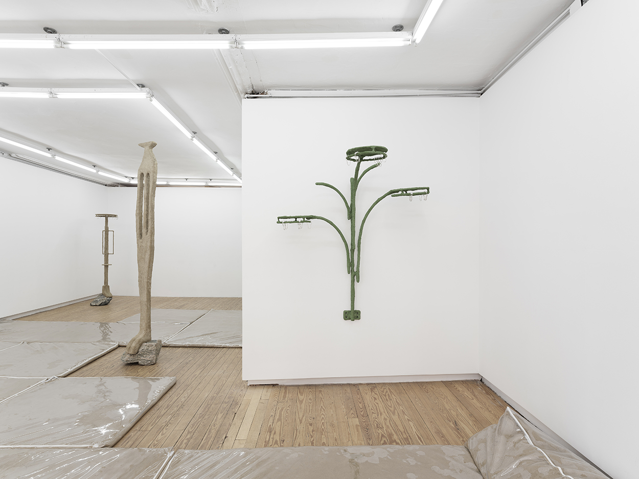 In the foreground, a green sculpture is affixed to the wall. It looks like a cross between a plant and a three-headed shower. In the background, two vertical, abstracted caryatid-like sculptures perch atop rocks. On the floor are clear vinyl furniture covers fliled with sand.