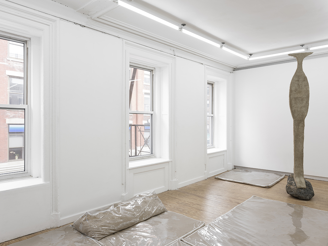one flattish, abstract caryatid-like sculpture made of sand perches atop a chunky rock in a gallery. On the floor, there are clear plastic furniture covers filled with sand.