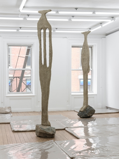 Two flattish, abstract caryatid-like sculptures made of sand perch atop chunky rocks in a gallery. On the floor, there are clear plastic furniture covers filled with sand.