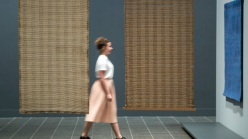 A woman in a white shirt and pink skirt walks past two large brown weavings hanging vertically on a blue wall