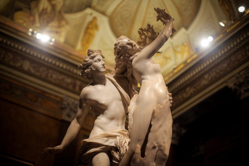 A marble statue shot from below showing a man chasing after a woman who is turning into a tree. Flowing drapery surrounds the man.