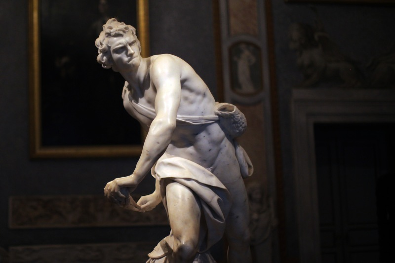 A marble sculpture of a man arching back with drapery flowing around him.