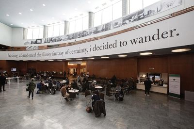 A large banner with a poetic quote hangs from the mezzanine in a library's lobby