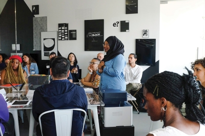 A dark-skinned woman wearing a black headscarf stands in the middle a room of seated people with thoughtful expressions. Everyone is looking at and listening to someone off-camera