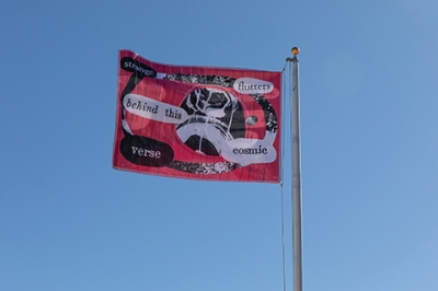 A red flag with black and white art and lettering waves against a clear blue sky