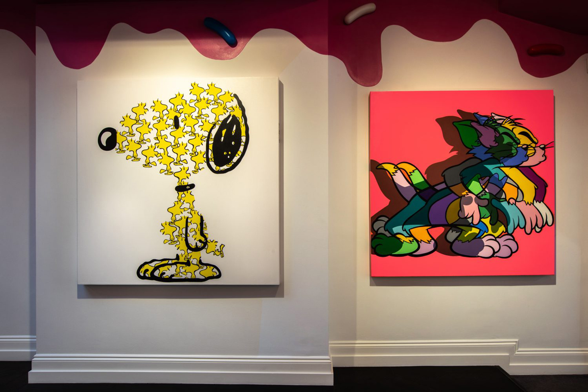Installation view of works by Jerkface, at Maddox Gallery. At left, a work of Snoopy made up of several Woodstock birds. At right, multiple Tom (from Tom and Jerry) superimposed on each other.