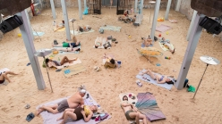 An industrial space plays home to a makeshift beach, with sand and sunbathers spread among poles.