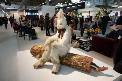 Life sized rabbit sitting on a log in the middle of the Armory Show
