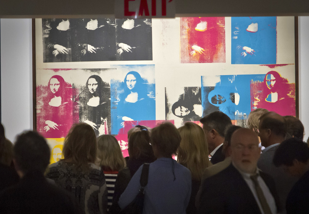 """FILE - In this May 1, 2015 file photo, visitors gather around Andy Warhol's silkscreen """"Colored Mona Lisa,"""" during Christie's Spring 2015 Evening Sale press preview in New York. Spirited bidding is expected Wednesday, May 13, at a New York City contemporary art auction highlighted by iconic works by Lucian Freud, Francis Bacon and others. Exhibited in many major exhibitions, it is estimated to bring about $35 million. (AP Photo/Bebeto Matthews, File)"""