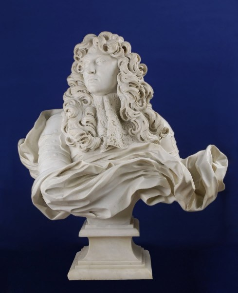 A marble bust of a man with flowing locks and flowing drapery.