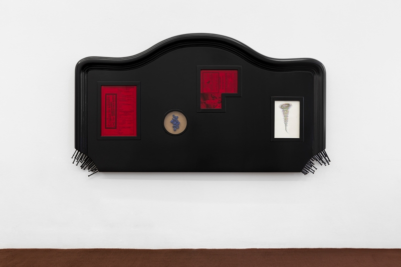 A black wooden headbord with a bunch of nails coming out of the bottom two corners. There are also two red rectangles, one white one, and a circle with images on them, but the details aren't very legible.