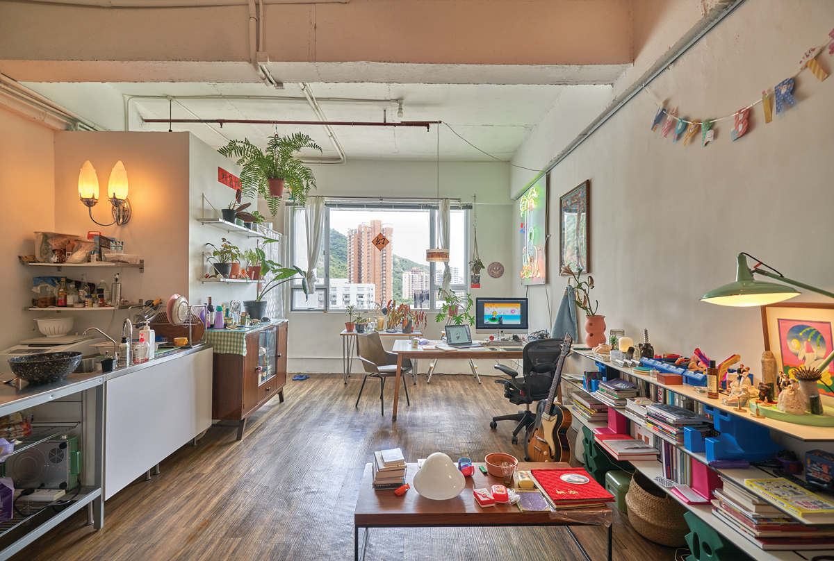 View of the inside of Wong Ping's modest Hong Kong studio, with a large table, kitchen area, shelves with palnts and books.