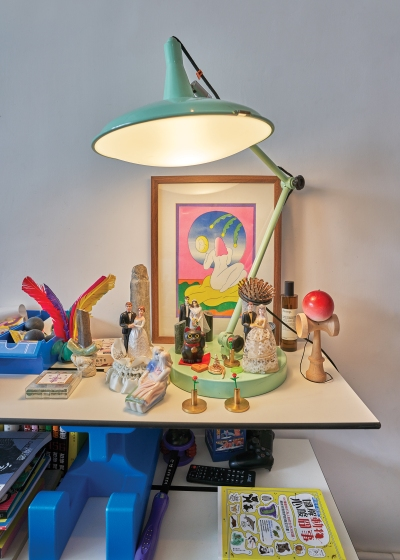 A shelf in Wong Ping's studio displaying various trinkets and objects and a large sea foam green lamp.