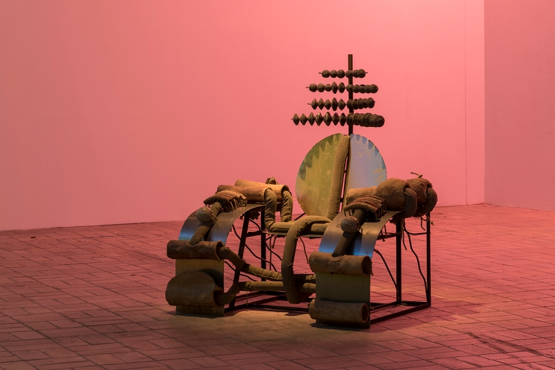 An absurdist chair sculpture with an abacus-like fixture above the back and stuffed tubes lining a metal armature. It's in a gallery and cast in pink light.