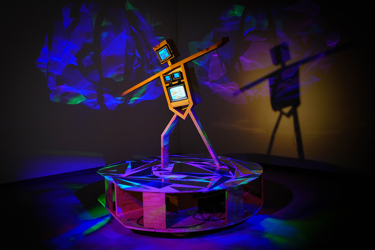 A robot-like sculpture made out of four TV-like monitors appears skateboarding. The figure is standing on a plinth that has shards of mirrors on it, and colorful lights are projected and refracted around the sculptuer.