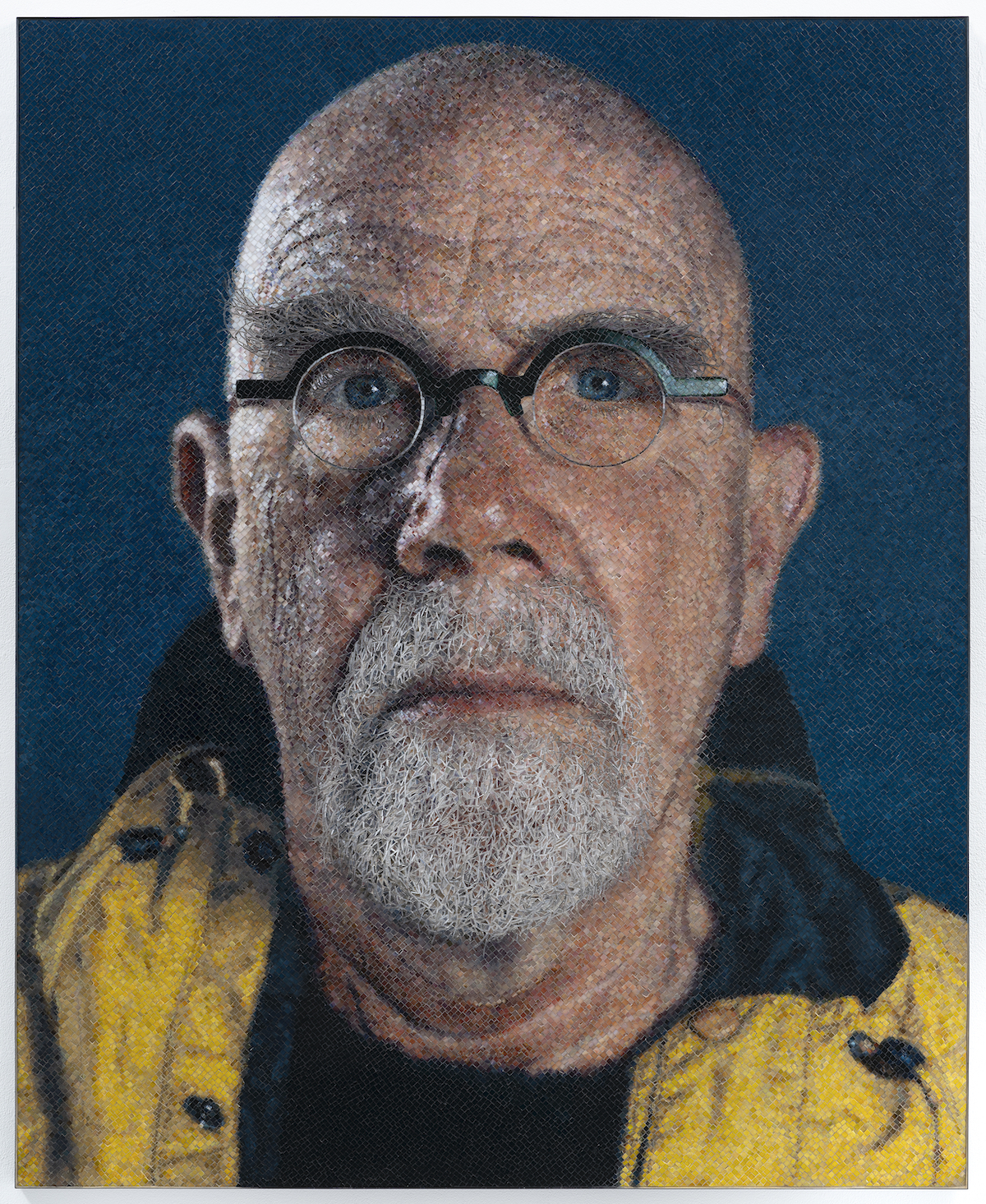A portrait of a white man with a goatee and glasses wearing a yellow jacket.