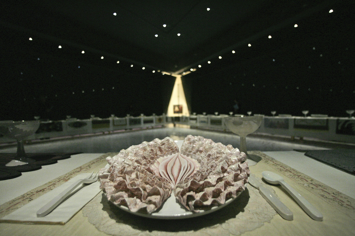 A plate resembling a vagina with frills with utensils next to it on a triangular table.