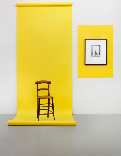 A bright yellow roll of paper hangs from the wall and onto the floor, where it runs underneath a wooden chair. To the right, on top of a rectangle of paint in the same hue, hangs a black-and-white photograph of Godard.